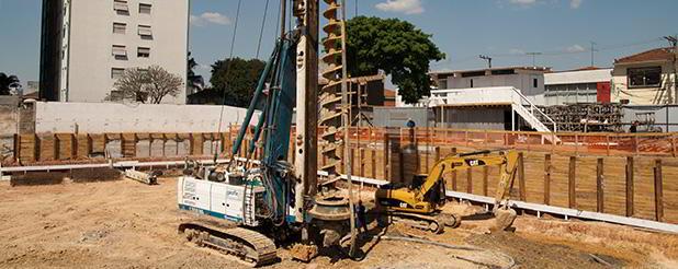 Perfuratriz e escavadeira em obra de fundação